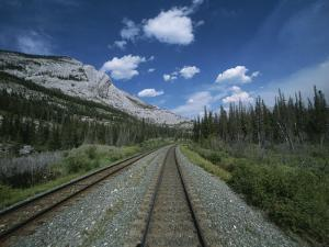 Train Tracks Winding Their Way Through the Canadian Rockies by Todd Gipstein