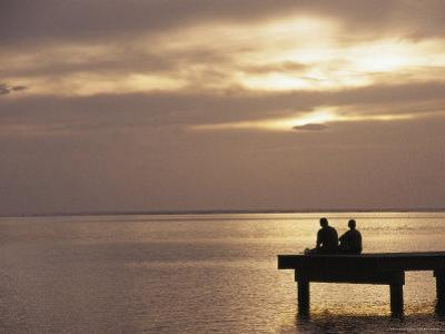 Two People Fishing on a Pier Looking Out at Sunset over the Pacific Ocean by Todd Gipstein