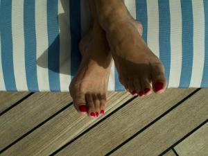Woman's Feet on a Striped Cushion on the Deck of a Cruise Ship by Todd Gipstein