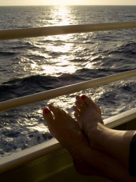 Woman's Feet Resting on the Railing of a Cruise Ship at Sunset by Todd Gipstein