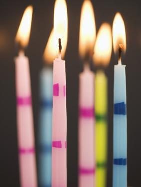 Six Lit Birthday Candles by Tom Grill