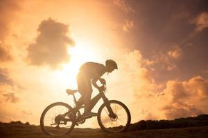 The Silhouette of Mountain Bicycle Rider on the Hill by Tom Wang