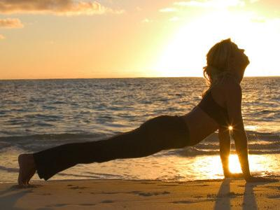 Woman Stretching on Beach by Tomas del Amo