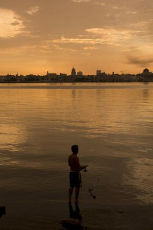A Cuban Fishing off the City of Havana. in between the Capitol Building. Cuba by Toniflap