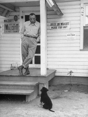 Boxer Joe Walcott Standing Outside Doorway of Building at Training Camp by Tony Linck
