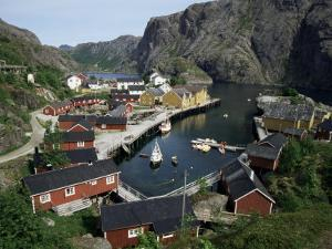 Wooden Red Houses on Stilts Over Water at the Fishing Village of Nusfjord, Lofoten Islands, Norway by Tony Waltham