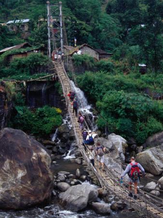 People Crossing Sagging Suspension Bridge Over Khudi Khola on Annapurna Circuit, Nepal