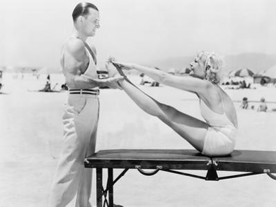 Trainer and Young Woman Doing Exercises at the Beach