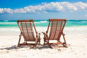Beach Wooden Chairs for Vacations and Relax on Tropical White Sand Beach in Tulum, Mexico by TravnikovStudio