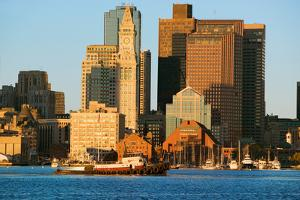 Tugboat with Boston Harbor and the Boston skyline at sunrise as seen from South Boston, Massachu...