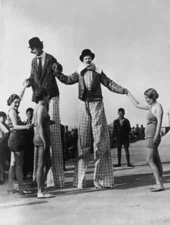 Two Clowns on Stilts Assisted by Girls in Bathing Costumes at Ramsgate Kent England