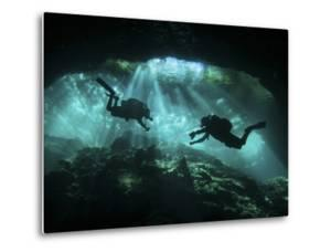 Two Divers Silhouetted in Light at Entrance to Chac Mool Cenote, Mexico