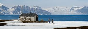 Two Hikers Standing on the Beach Near a Hunting Cabin, Bellsund, Spitsbergen, Svalbard Islands