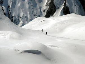 Two Mountain Hikers are Dwarfed by the Winter Landscape of the Formazza Valley
