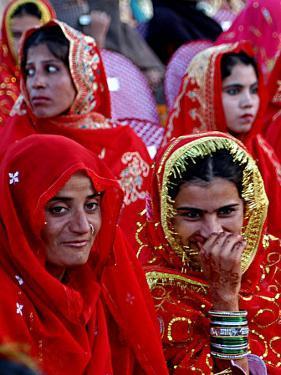 Two Pakistani Brides, Smile During a Mass Wedding Ceremon
