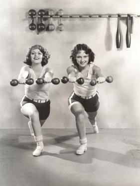 Two Women Exercising with Dumbbells at Gym