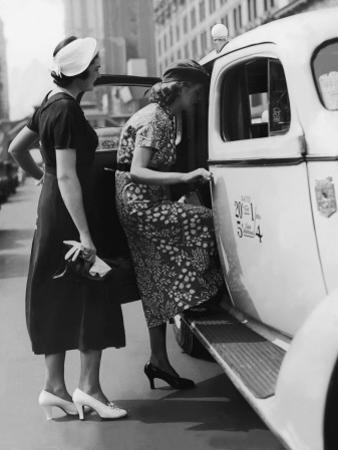 Two Women Getting in a Taxi on an Urban Street, 1950's