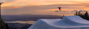 Freestyle skier doing a trick off a jump above city at sunset, Canada, North America by Tyler Lillico