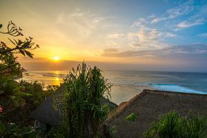 Surfers at sunset in Bali with straw roofed huts, Indonesia, Southeast Asia, Asia by Tyler Lillico