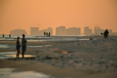 People strolling the beach at Destin at twilight. by Tyrone Turner