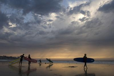 Surfers get ready to hit the waves at sunset, despite water pollution. by Tyrone Turner
