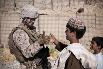 U.S. Marine Thumb Wrestles with an Afghan Boy