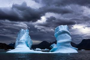 A Shimmering Blue Iceberg with Two Towers, under a Gray Stormy Sky by Uli Kunz