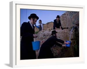 Ultra-Orthodox Jewish Men Stand Next to a Well as They Fill Canisters with Water in Jerusalem