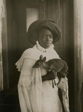 A Stylish Young Kenyan Woman Holding Her Pet Deer by Underwood & Underwood