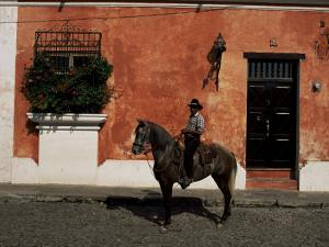 Man on Horse in Front of a Typical Painted Wall, Antigua, Guatemala, Central America by Upperhall