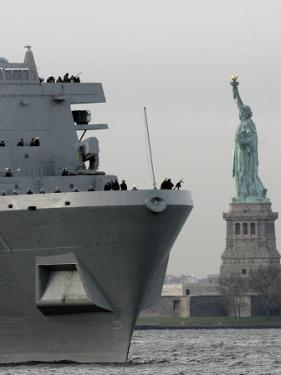 USS New York Passes the Statue of Liberty While Fireboats Spray Water in New York