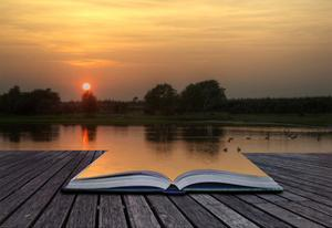 Creatice Concept Image Of Setting Sun Reflected In Still Lake Water Coming Out Of Pages by Veneratio