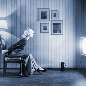 Young Woman Sitting on a Chair in Vintage Interior and Watching Retro TV by viczast