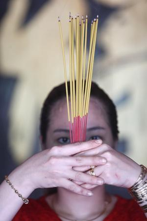 https://imgc.allpostersimages.com/img/posters/vietnamese-woman-in-red-traditional-long-dress-ao-dai-praying-with-incense-sticks_u-L-Q1GYM1N0.jpg?artPerspective=n