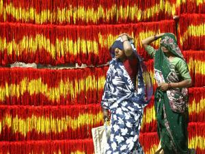 Villagers Walk Past Freshly Dyed Kalawa, a Sacred Orange-Yellow Thread Used in Hindu Rituals