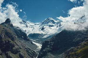 Snow Capped Alpine Mountains. Trek near Matterhorn Mount. View of the Mountain and Valley of a Moun by vitaliymateha