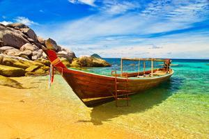Thai Longtail Boat Anchored in a Turqouise Bay by vitalytitov