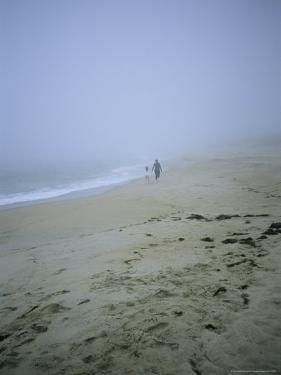 Mother and Child Walk Hand in Hand on a Misty Beach by Vlad Kharitonov