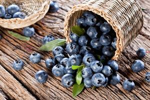 Blueberries Have Dropped from the Basket on an Old Wooden Table. by Volff
