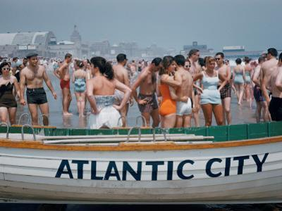 Throngs of Swimmers Stroll Behind a Wooden Lifeboat on the Beach