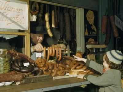 Vendor Holds Up Sausages for Young Girl to Point Out Her Selection