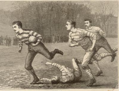 An Attacking Player Charges Forward with the Ball Chased by Two Opposing Players