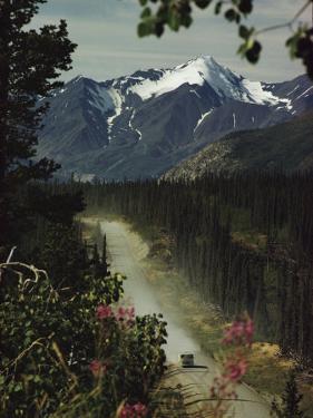 A Camper Rolls Down a Dirt Road Below High Mountains in Alaska by W. E. Garrett