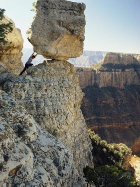 A Man Pretends to Push a Huge Boulder into the Canyon by W. E. Garrett