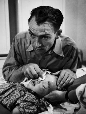 Country Dr. Ernest Ceriani Aftter girl gets stiches from being kicked in head by a Horse by W. Eugene Smith