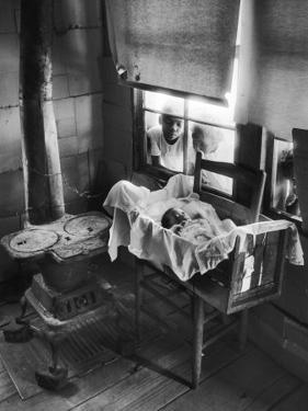 Victoria Cooper's Children Peering in Window Where Newborn Baby Lies in Crib Made from Fruit Crate by W. Eugene Smith