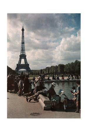 A Crowd Watches Children Sail Boats in a Pond Near the Eiffel Tower