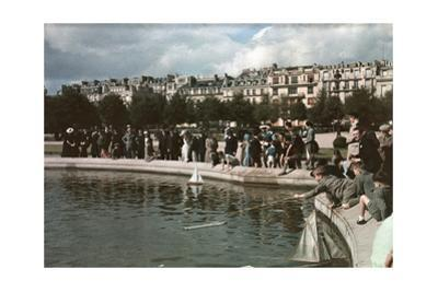 A Crowd Watches Little Boys Have Small Boat Races in a Pond
