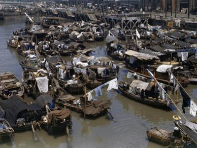 Drying Laundry Hangs from Poles on Houseboats Clustered in a Canal
