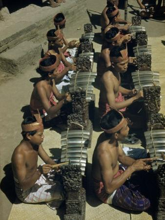Musicians Sitting Cross-Legged Play Xylophones with Bronze Keys